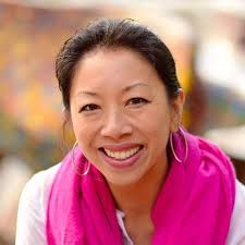 Jen Soriano head shot. A smiling Filipina with hoop earings and a bright pink scarf
