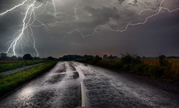 Lightning strikes in a stormy sky next to a wet road in the country