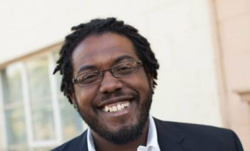 photo of Aaron Goggans, a black man with short dreadlocks, in a blue blazer, white collared shirt, glasses, and smiling